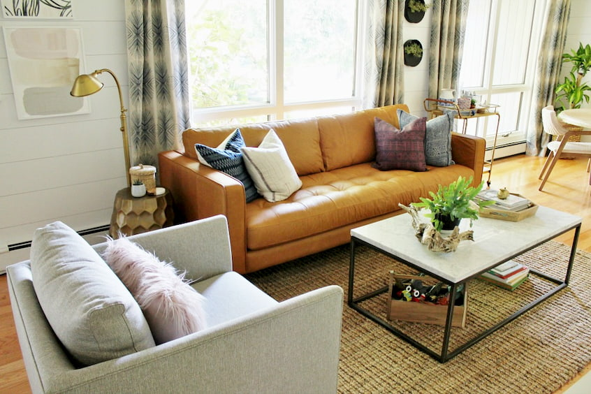 orange modern sofa with cushions and curtains