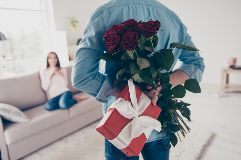 man hiding bouquet of red roses