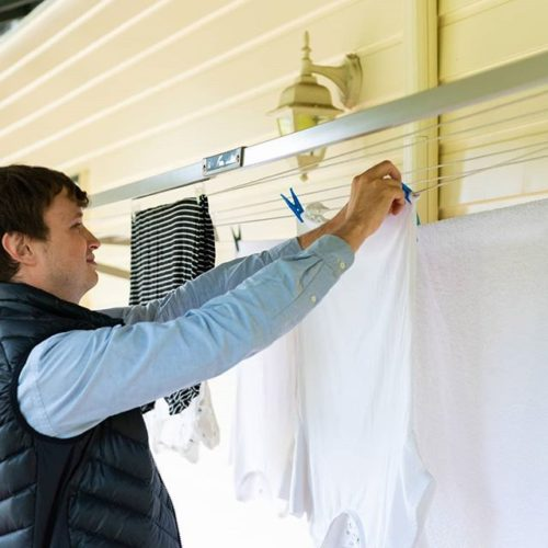 man hanging clothes on a folding rack