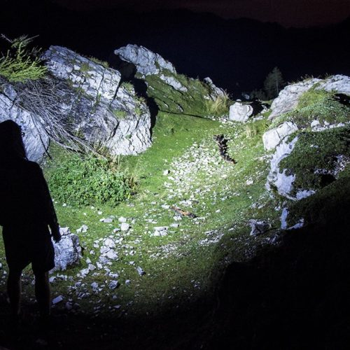 picture of a person with a olight military flashlight in the mountains