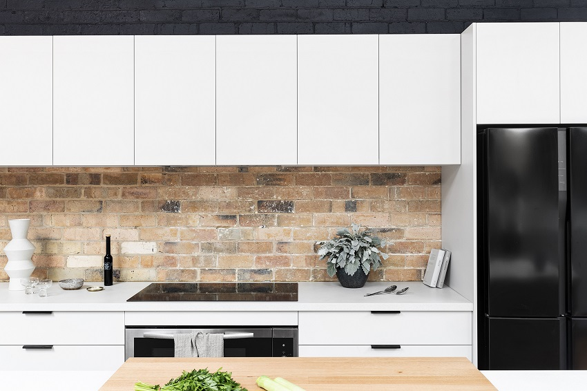 picture of modern kitchen with brick wall, white flat pack cabinets and black fridge